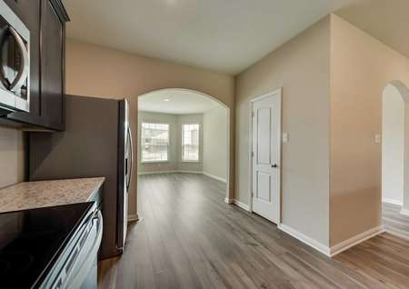 The kitchen with wood-like flooring, a pantry and brand new kitchen appliances in the Texoma floor plan.