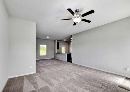 Carson family room with overhead brown fan, carpeted floors, and gray walls with white trim
