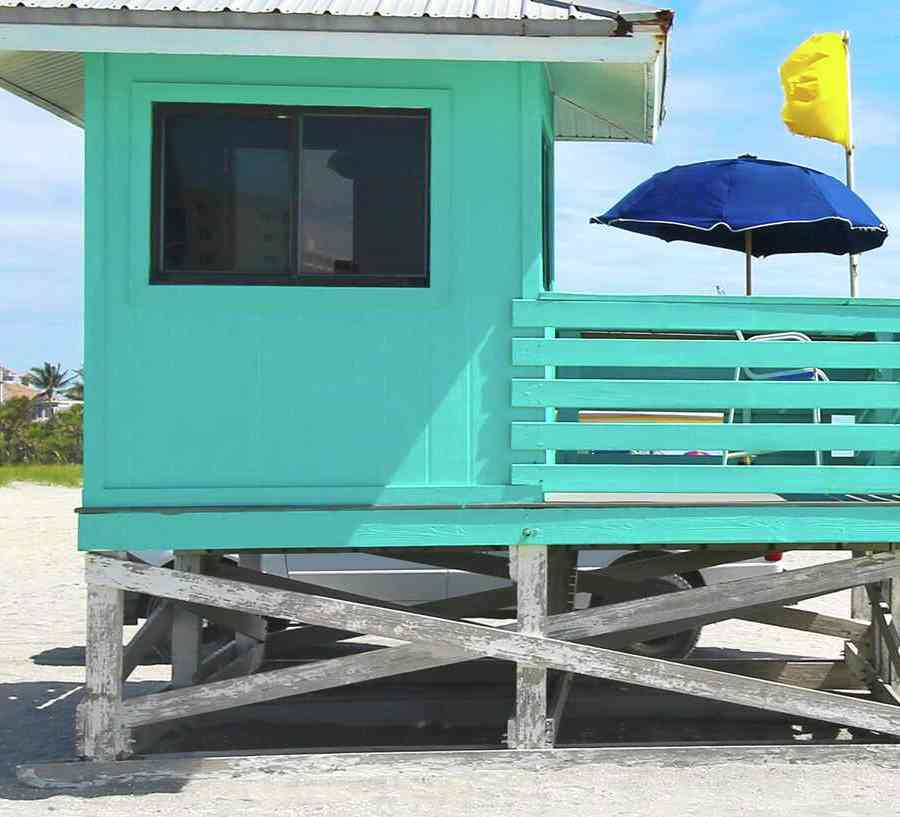 Sarasota, Florida turquoise lifeguard station with blue sun-umbrella, white sandy beach, and turquoise waters