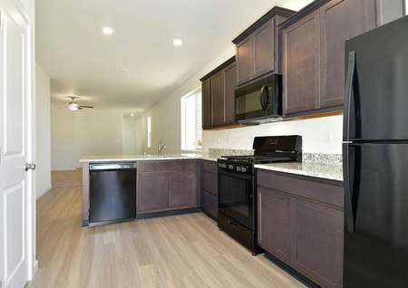 Aspen kitchen with black appliances, brown cabinetry, and granite countertops