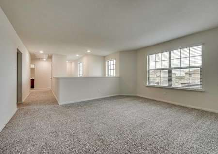 Upstairs flex space with front windows, white walls and brown carpet.