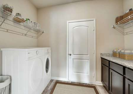 Staged Oakmont laundry room with washer and dryer, upper shelves, granite countertops on brown cabinets and white entry door