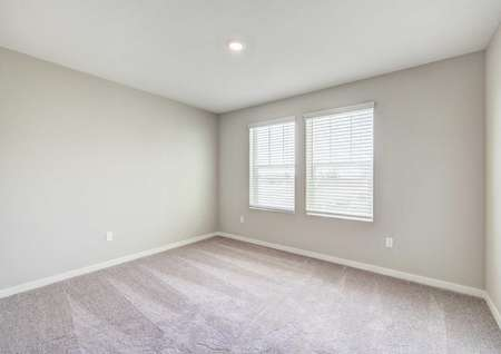 A secondary bedroom in the Crystal floor plan with carpet flooring, two windows andrecessed lighting.