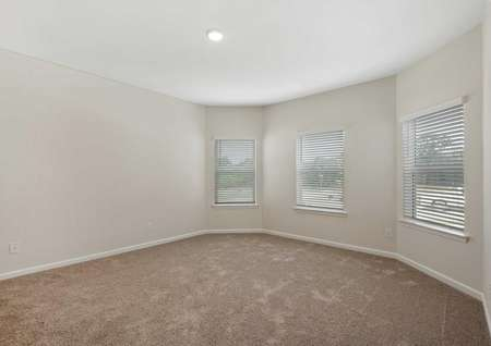 The Cypress floor plan's master bedroom with brown carpet with white baseboards and three large windows with 2