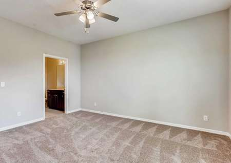 Picture of the master bedroom in the Santa Maria model home. The walk-in closet and master bathroom entry are visible