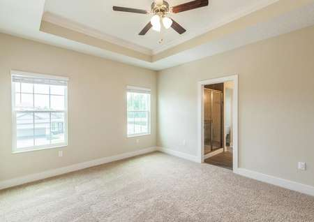 Secluded primary bedroom featuring a vaulted ceiling with a fan, two windows and its own full bathroom with a walk-in closet.