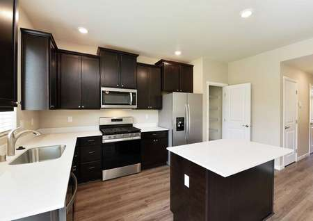 The Northwest Cypress kitchen is shown with dark brown cabinets and white quartz countertops and a kitchen island.