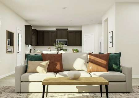 Rendering showing   the view from the living room towards the kitchen. The living space has a   light gray couch and rectangular coffee table sitting on a light-colored rug.