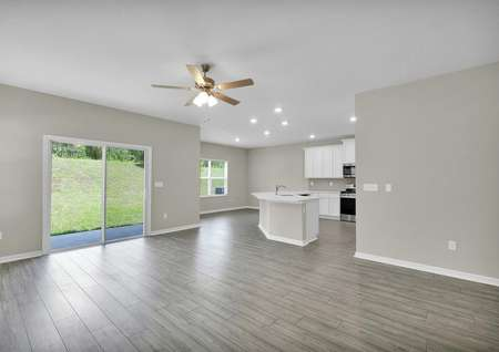 View of the family room, dining room and kitchen with natural light throughout the entertainment space.