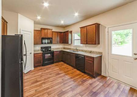 Granite countertops, vinyl wood-style flooring, dark brown cabinets and black appliances in the kitchen of the Chatuge floor plan