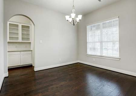 Bradley dining room with chandelier, wood flooring, and fontyard facing window with blinds