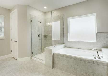 Master bath with granite counters, walk-in shower, garden tub, tile flooring, and white cabinets in the Bradley floor plan