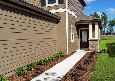 A walkway on the side of the home with plants along both sides that leads to the front door of the Tomoka floor plan.