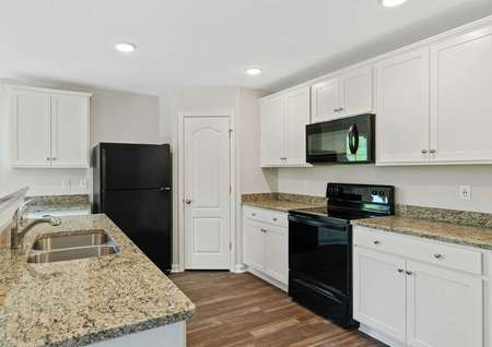 Avery home kitchen with brown granite counters and black appliances