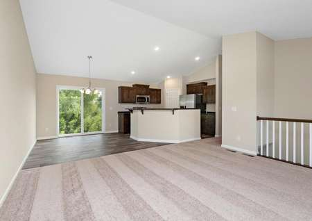 View from carpeted living room into dining and kitchen.