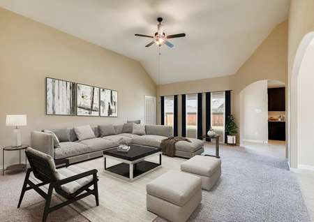 Staged spacious living room with raised ceilings, ceiling fan, three windows to backyard with drapes, sectional sofa, coffee and end tables, area rug on carpet.