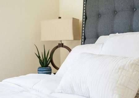 Home staged with bedroom furniture including bed with white sheets, grey headboard, and modern lamp