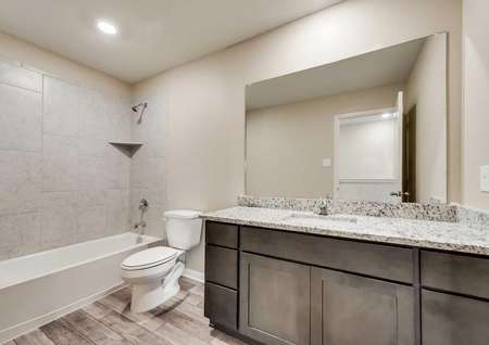 Ozark bathroom with large granite vanity, wood cabinetry, and shower/tub combo