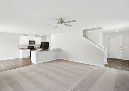 Burke great room with tan carpets, granite kitchen, and staircase