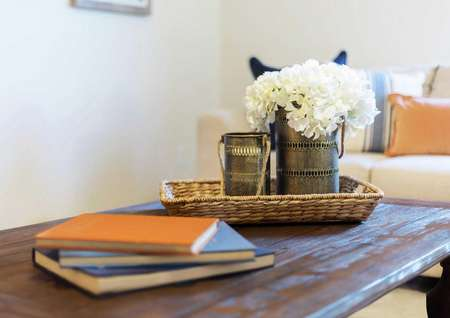 The Madison staged model home with books, woven tray, and white flowers in a coffee can on a wooden table