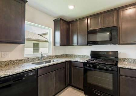 TheAnastasia floor plans kitchen with tile floors, dark wood cabinets, agas stove range and all black appliances.