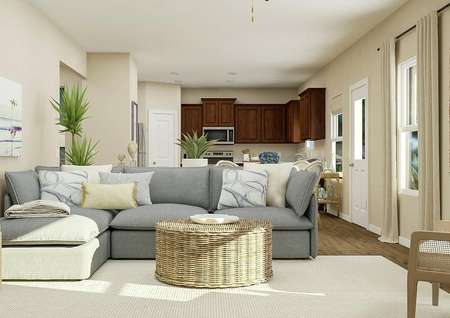 Rendering of the   living room with two windows, tan walls and wood look flooring covered by a   light-colored rug. Decorated with a large sectional couch and round wicker   coffee table.