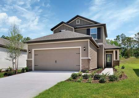 Large, two-story home with a two-car garage, a covered entryway and brown siding.