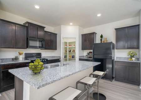 Laguna kitchen with bar stools, granite counter, and recessed lights