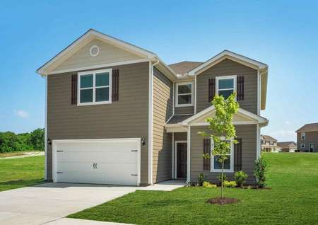 The Exterior of the 2 story Driftwood model home is equipped with light brown and tan siding, white trim, white gutters, shutters on the windows, 2 car garage, and landscaped yard