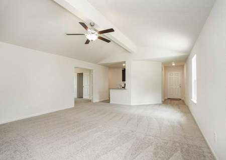 Pecos great room with carpeted floors wall-to-wall, overhead ceiling fan, and white on white wall paint