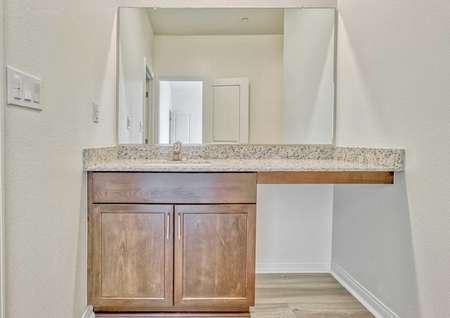 A part of the bathroom in the Sunflower floor plan with a sink, granite countertops, brown cabinets and a mirror.