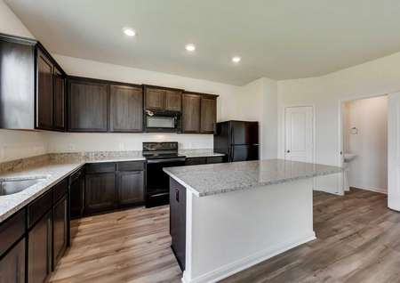 Jaguar kitchen with recessed lights, dark wood cabinets, and granite countertops