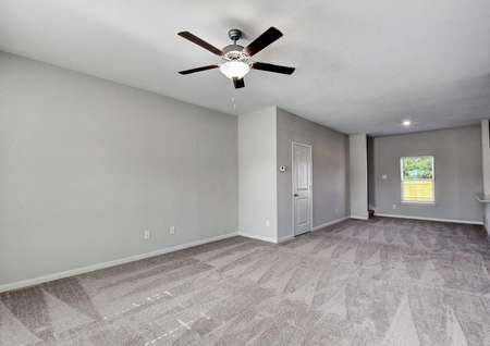 Carson living room with gray carpeting, overhead fan, and gray walls with white trim and white doors