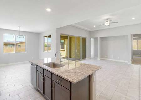 Bartlett kitchen and family room with built-in entertainment center, ceramic floors, and granite island with sink