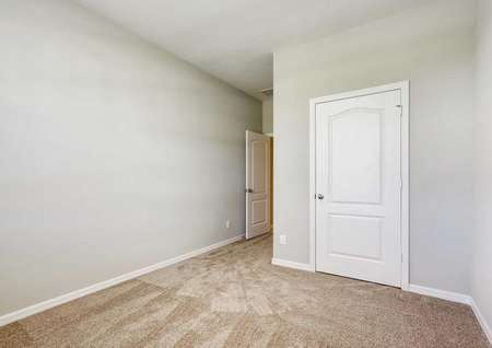 A bedroom in the Patricio model home with tan carpet, white baseboards and light tan walls