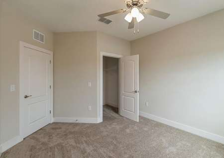 Spacious, carpeted bedroom with a ceiling fan and a large walk-in closet.