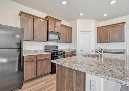 Aster kitchen with brown cabinetry, black oven / stove, and wood flooring