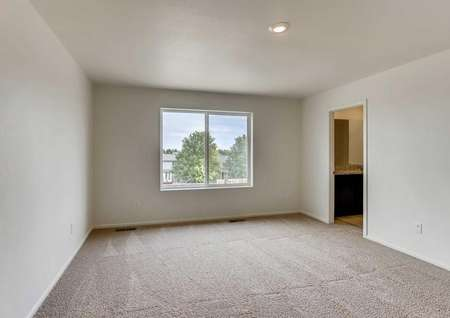 Columbia bedroom with private bathroom, large two pane window, and light brown carpet