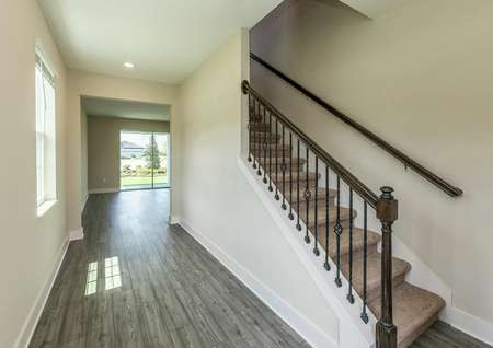 A beautiful staircase and luxury vinyl plank flooring at the home's entrance.