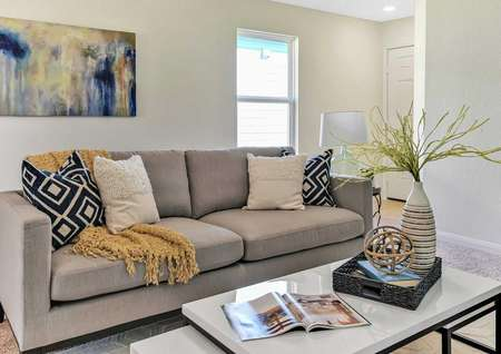 Walnut staged home with gray sofa with white and gray and black pillows, coffee table with open magazine and decoration and wall art hanging on the wall
