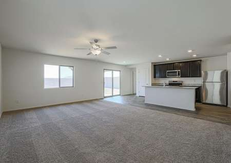 Spacious living room with tan carpet, ceiling fan and a great open-concept layout.