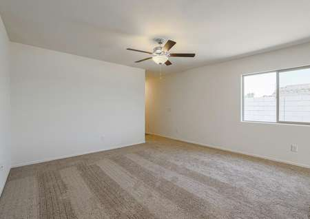 Open family room with tan carpet and a ceiling fan.