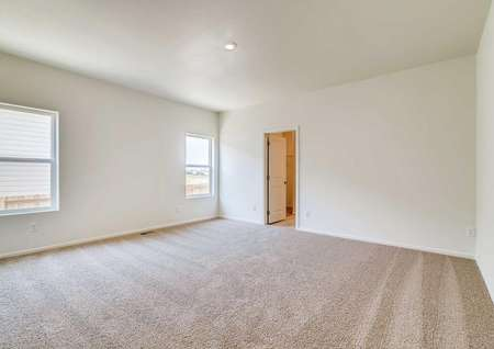 Pike floor plan's master bedroom with light colored carpet and white walls.