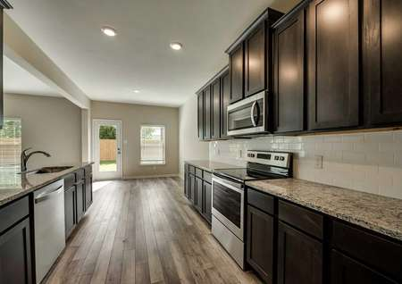 Oakmontfloor plans kitchen with woodlike floors and stainless steel appliances.