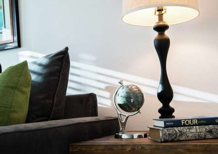 Sea Forest Beach Club model home staged with dark blue sofa and a small globe and lamp sitting on side table