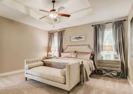 Staged master bedroom with king bed, taupe and silver decor, two windwos with gray silk drapes, upholstered bench, double nightstands and lamps, ceiling fan, coffered ceiling.