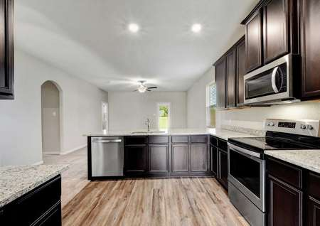 Fannin kitchen and great room with recessed lighting, wooden floors, and granite top brown cabinets