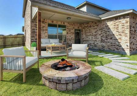 Staged back yard with a fire pit and sitting area.