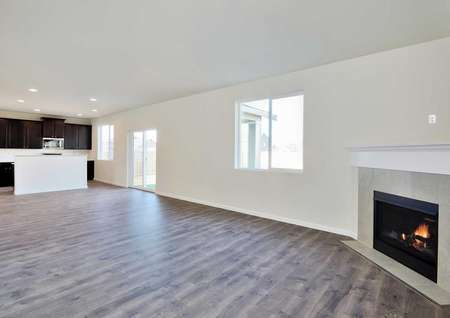 The Mercer plan's spacious living room with hardwood floors and a fireplace. The upgraded kitchen is in the back of the image