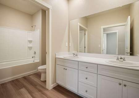 Secondary bathroom with white dual-sink vanity.